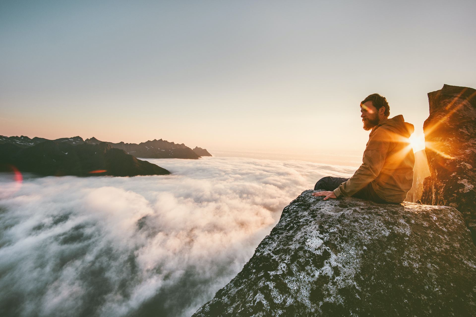 Man relaxing alone on the edge cliff  mountain above clouds travel adventure lifestyle harmony with nature vacations in Norway