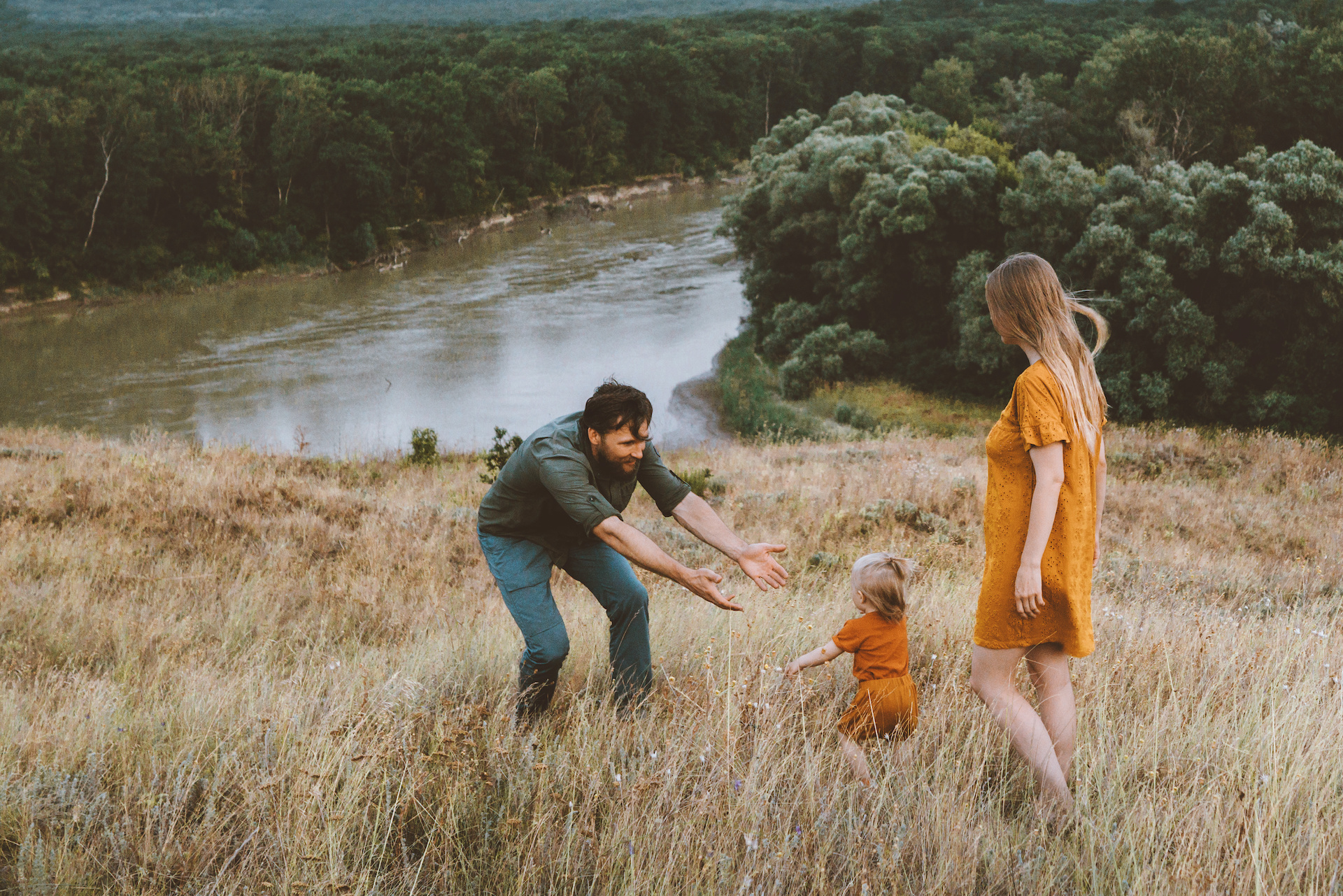Parents walking with child outdoor family vacation mother and father with baby toddler healthy lifestyle countryside nature river and forest view